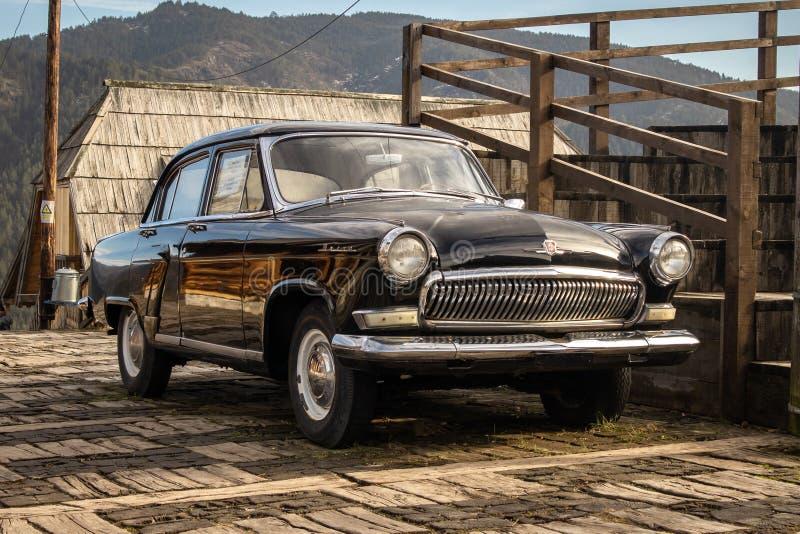 Oldtimer car Volga GAZ-21 built in a soviet Russia in traditional retro village stock photo