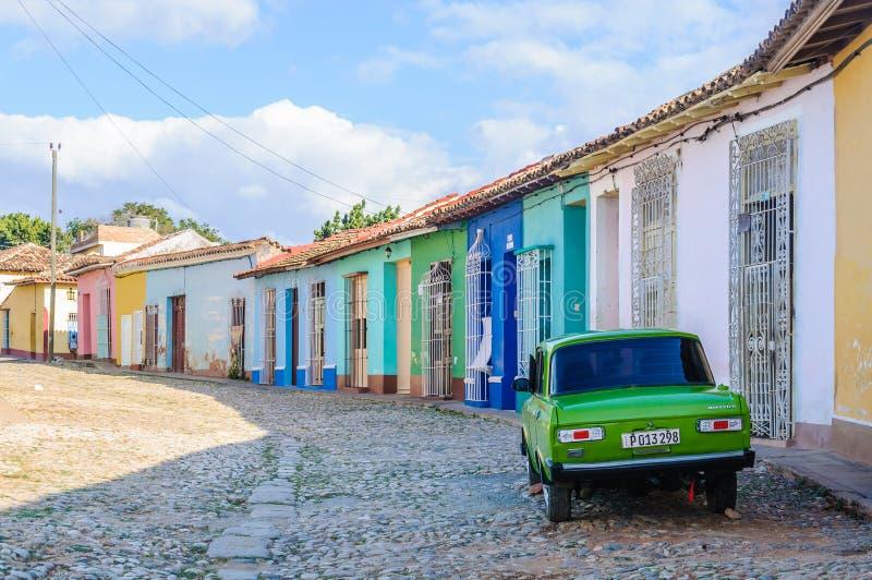 Oldtimer framme av färgrika hus i Trinidad, Kuba fotografering för bildbyråer