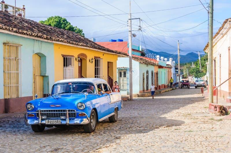 Oldtimer framme av färgrika hus i Trinidad, Kuba royaltyfri bild