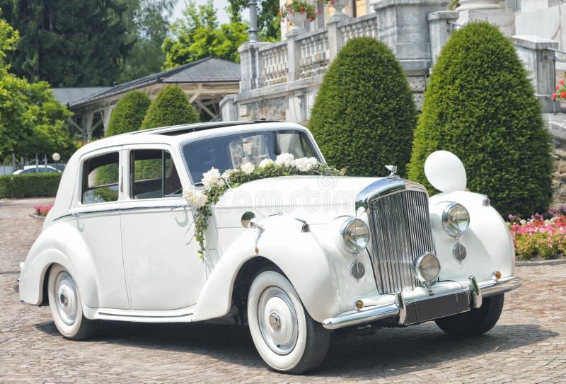 Oldtimerauto omhoog gekleed met witte bloemen voor huwelijksceremonie stock afbeelding