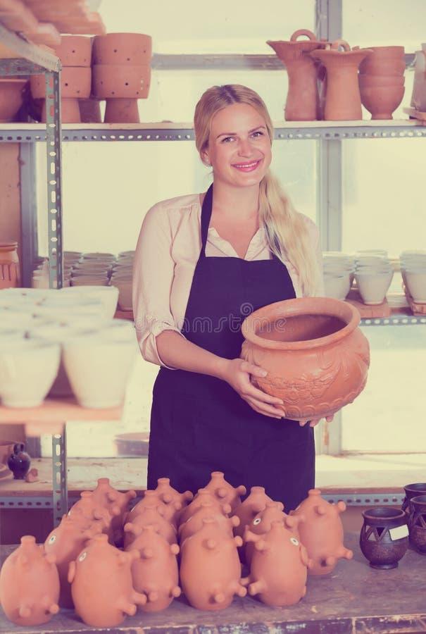 Oleiro contente da mulher que leva embarcações cerâmicas fotos de stock royalty free