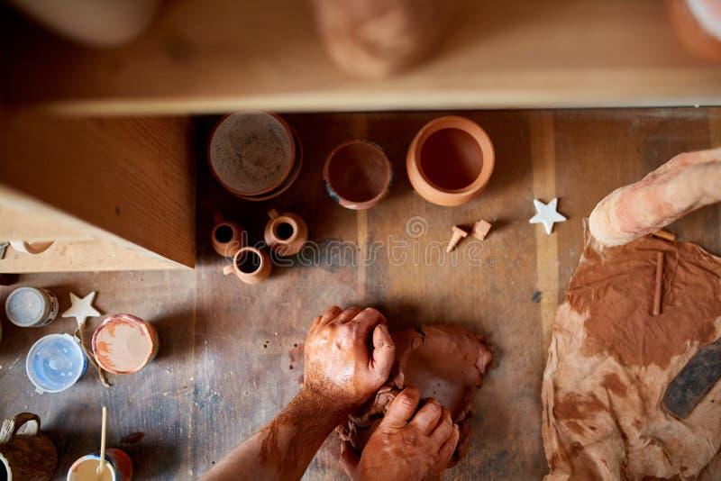 Oleiro masculino que molda uma argila na oficina da cerâmica, close-up, foco seletivo imagens de stock