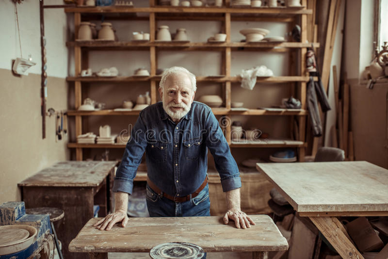 Oleiro superior que está e que inclina-se na tabela contra prateleiras com os bens da cerâmica na oficina imagens de stock