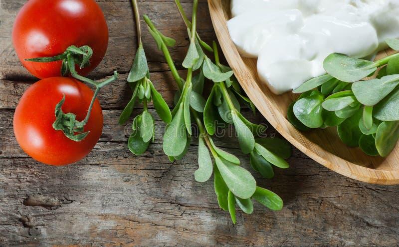 Oleracea fresco de Portulaca do purslane, ervas daninhas comestíveis com iogurte e tomates de cereja na tabela de madeira fotografia de stock royalty free