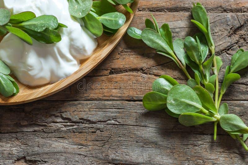 Oleracea fresco de Portulaca do purslane, ervas daninhas comestíveis com iogurte na tabela de madeira imagem de stock royalty free