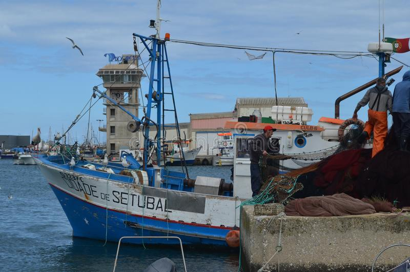 The crew of a purse seiner collects its nets in Olhao fishing harbour, Algarve, Southern Portugal. Olhão is a municipality and urban community in the Algarve royalty free stock image