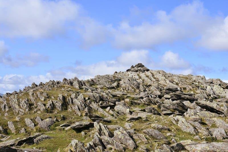 Olhando acima à cimeira rochoso de Hart Crag, distrito do lago imagem de stock