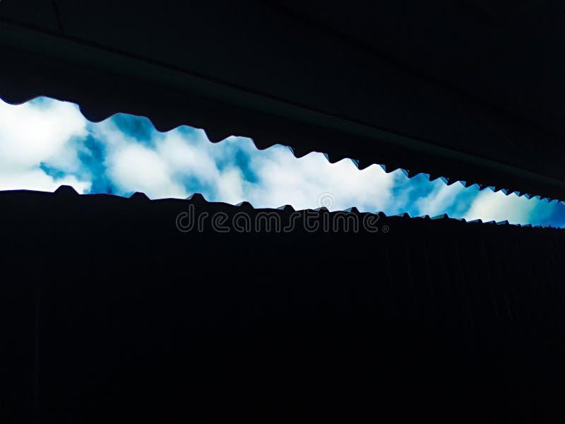 Olhando acima o telhado com céu azul e nuvens foto de stock