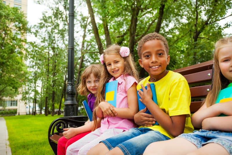 Olhando as crianças sentam-se junto no banco e sorriem-se fotos de stock