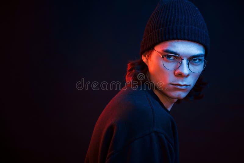 Olhando diretamente para a câmera Estúdio fotografado em estúdio escuro com luz neon Retrato de homem sério fotografia de stock royalty free