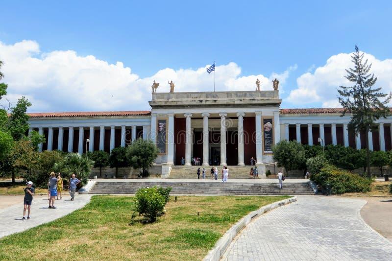 Olhando fora na parte dianteira do museu arqueológico nacional mundialmente famoso em Atenas, Grécia Diversos visitantes estão an fotografia de stock