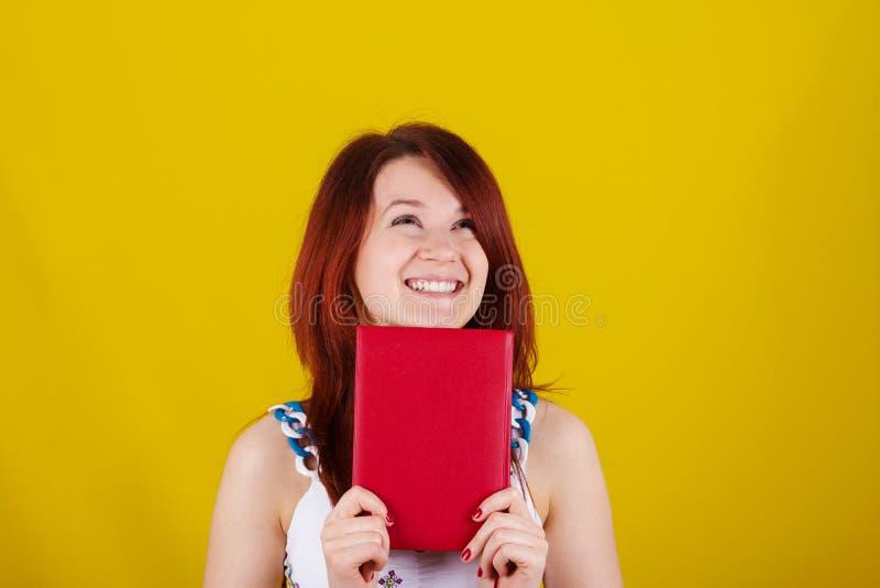Olhando o estudante novo acima de sorriso, menina da mulher que guarda um livro vermelho imagem de stock royalty free
