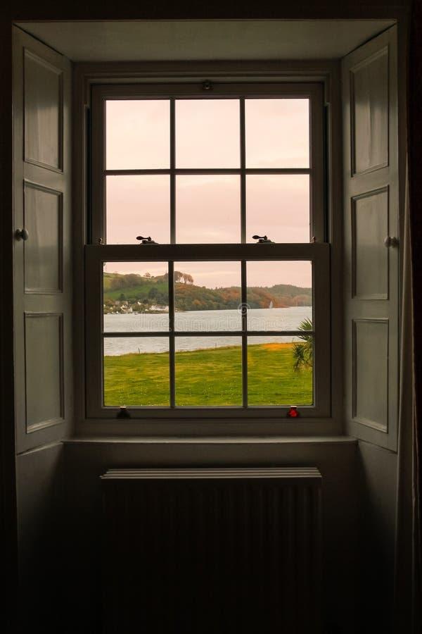 Olhando o nascer do sol através da janela fotos de stock royalty free