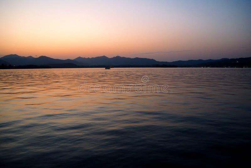 Olhando o sol vá para baixo sobre o lago sunset fotos de stock