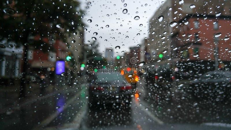 Olhando o tráfego através de um para-brisa coberto com os pingos de chuva, em um dia aborrecido e sombrio imagens de stock