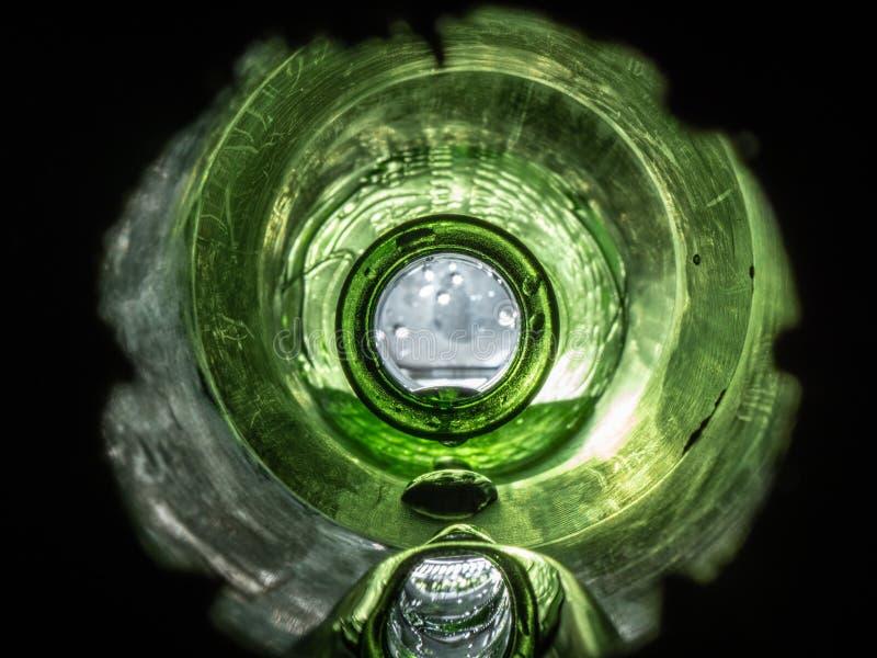 Olhar ascendente próximo em um gotejamento verde vibrante da garrafa molhado fotografia de stock royalty free