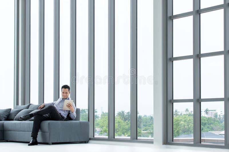 Olhar asiático novo do homem de negócios na tabuleta que senta-se no SMI feliz do sofá foto de stock royalty free