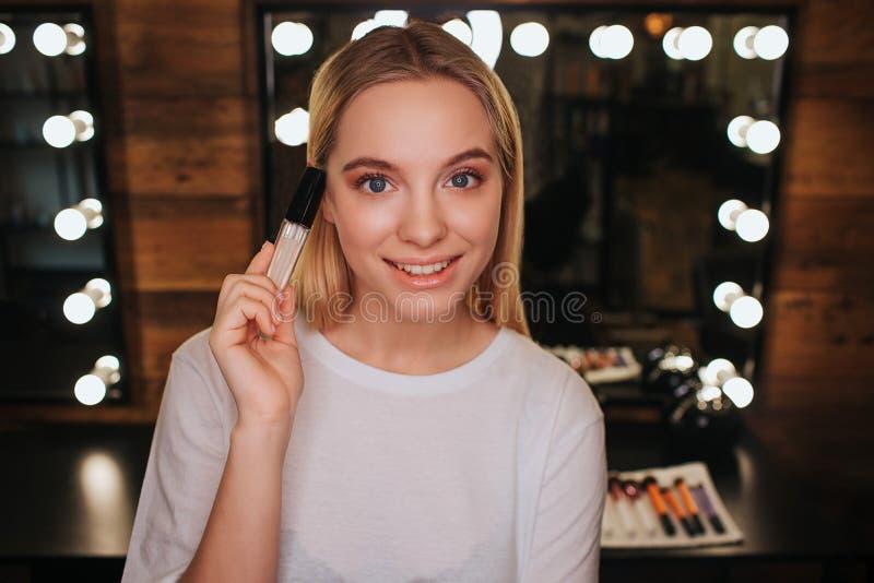 Olhar bonito agradável da jovem mulher na câmera e na pose Guarda lipgloss à disposição Mulher na sala da beleza Espelho com luz foto de stock