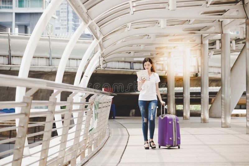Olhar bonito encantador da mulher do viajante em um mapa para encontrar um de imagens de stock royalty free
