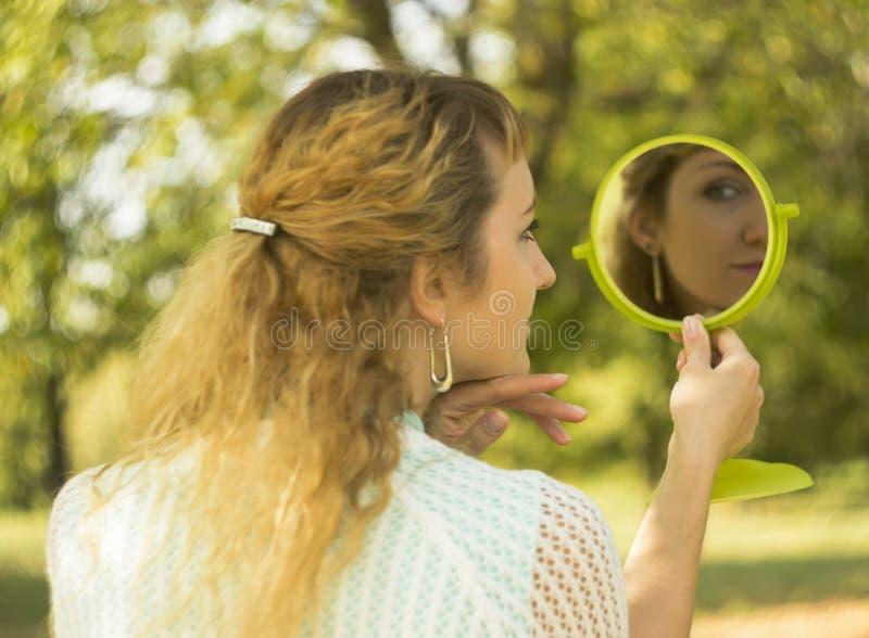 Olhar bonito novo da menina no espelho no parque Concepção do delicado e do borrão imagem de stock royalty free