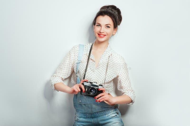 Olhar da forma, modelo consideravelmente fresco da jovem mulher com a c?mera retro que veste na roupa da sarja de Nimes que levan fotos de stock