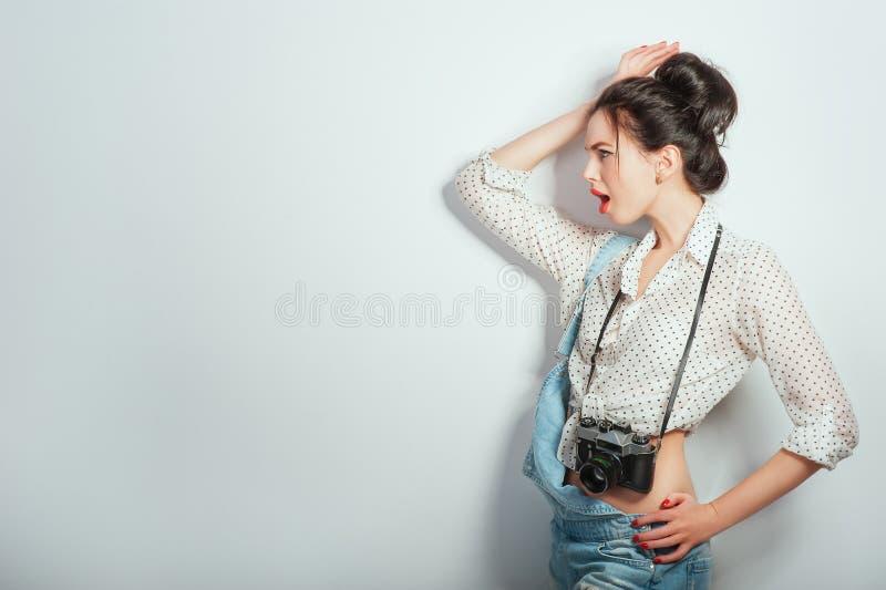 Olhar da forma, modelo consideravelmente fresco da jovem mulher com a c?mera retro que veste na roupa da sarja de Nimes que levan imagem de stock royalty free
