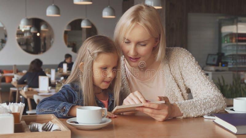 Olhar da mãe e da filha no menu imagem de stock