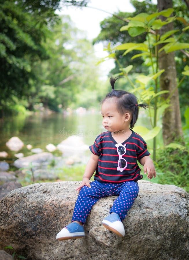 Olhar da menina da criança que senta-se em uma rocha fotografia de stock