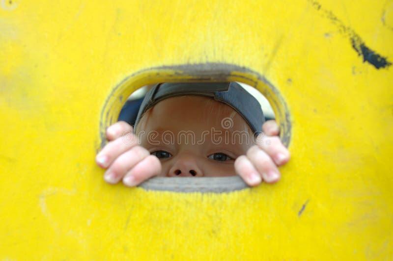 Olhar da menina fora do furo na parede pintada. foto de stock