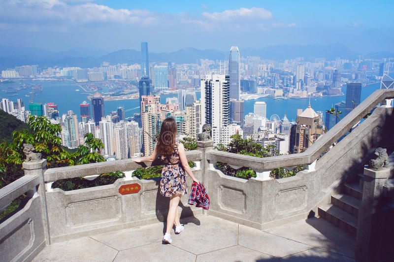 Olhar da menina no panorama das construções de Hong Kong da paridade de Victoria Peak imagens de stock royalty free