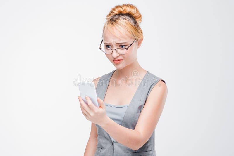 Olhar da moça no telefone com aversão e aversão fotografia de stock