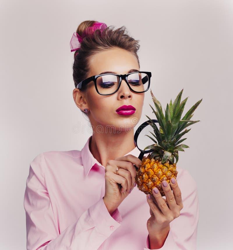 Olhar da mulher no abacaxi através da lupa foto de stock royalty free