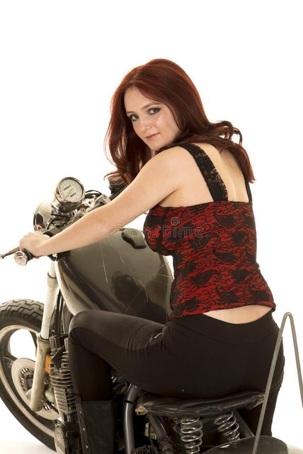 Olhar da parte traseira da motocicleta da parte superior vermelha da mulher foto de stock