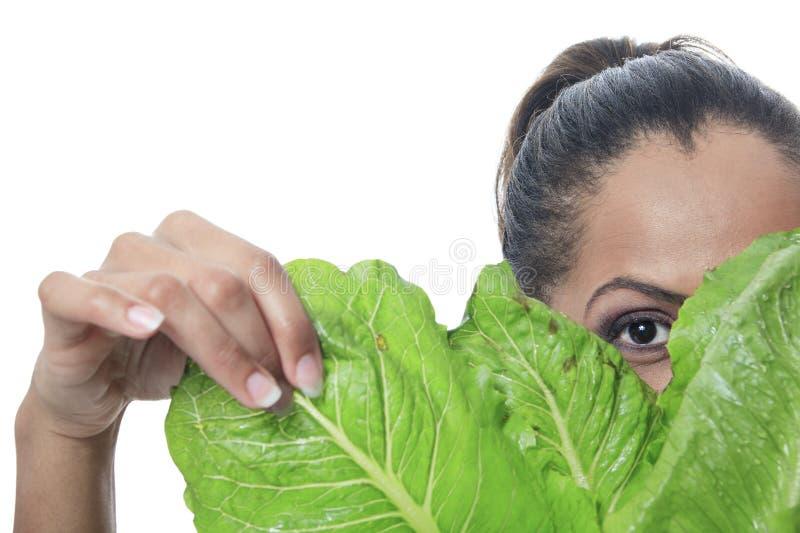 Olhar da pessoa do mulato através de uma salada foto de stock