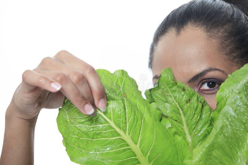 Olhar da pessoa do mulato através de uma salada foto de stock royalty free