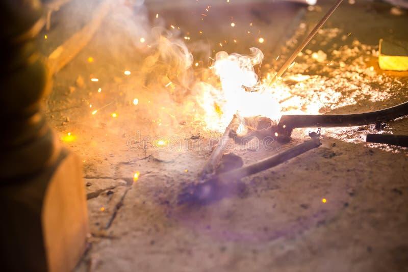Olhar das faíscas como foguetes soldando o aço aço labour da soldadura nas plantas da indústria fotografia de stock royalty free