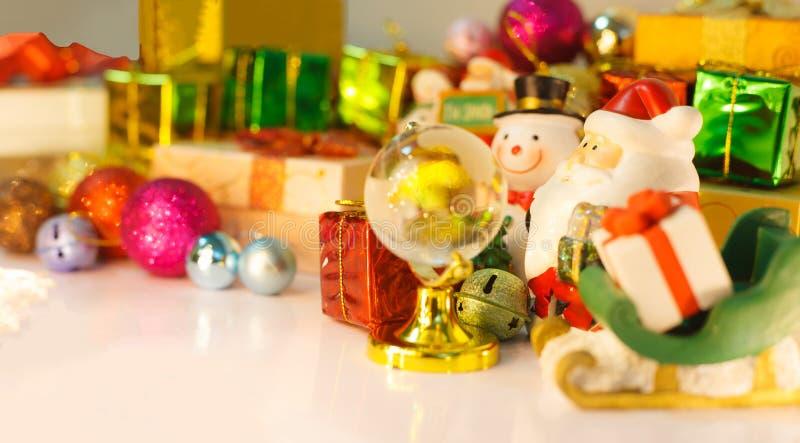 Olhar de Santa Claus e do boneco de neve no globo para que as boas crianças entreguem os presentes, fundo com as caixas decoradas fotografia de stock royalty free