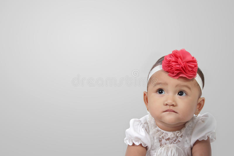 Olhar do bebê no copyspace no cinza foto de stock