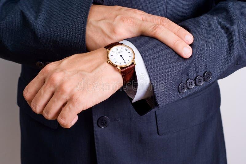 Olhar do homem de negócios seu relógio fotografia de stock royalty free