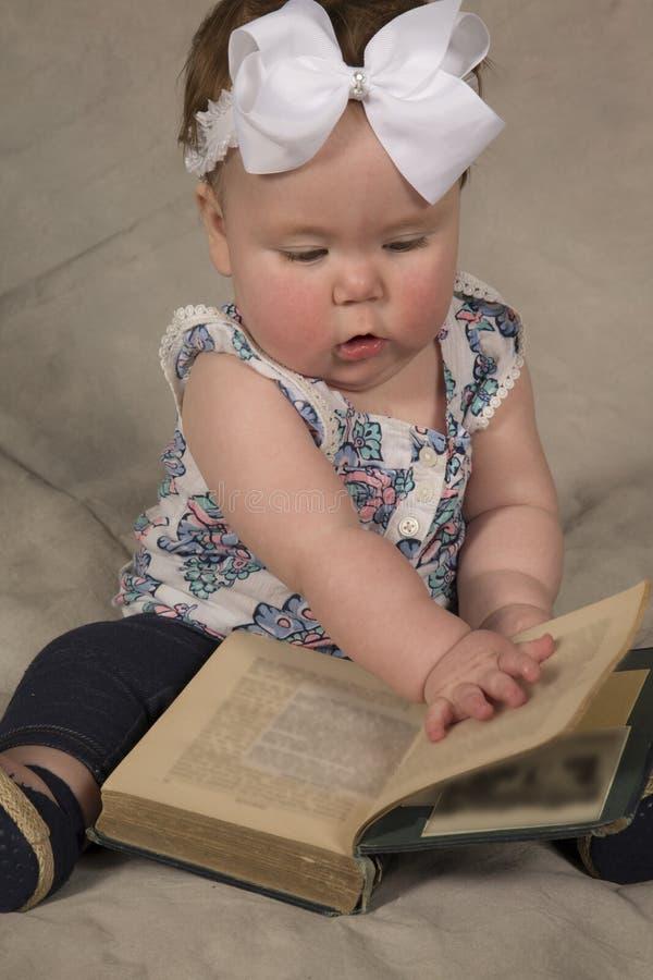 Olhar do livro de leitura do bebê para baixo foto de stock royalty free