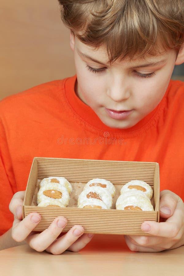 Olhar do menino na caixa aberta de cartão ondulado com biscoitos fotografia de stock royalty free