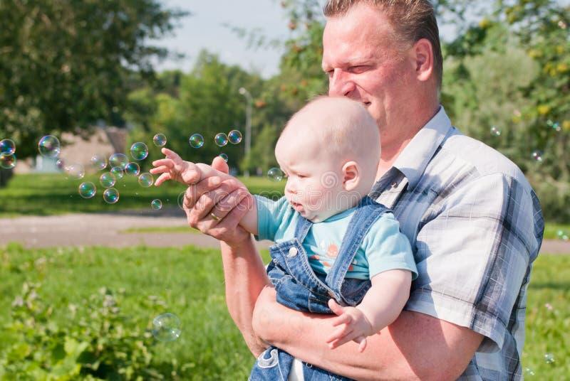 Olhar do paizinho e do filho nas bolhas imagens de stock royalty free