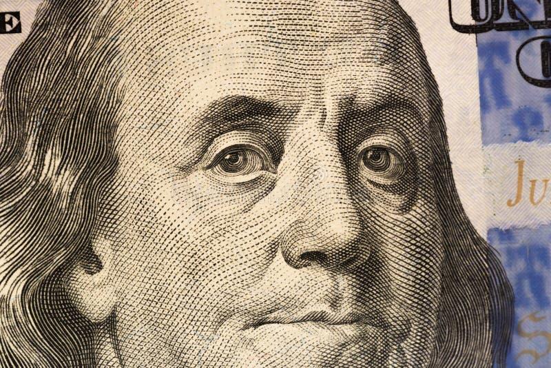 Olhar do ` s de Benjamin Franklin em cem notas de dólar r imagens de stock royalty free