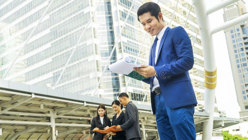 Olhar esperto do homem de negócio no documento no sentimento feliz em c urbano fotos de stock royalty free