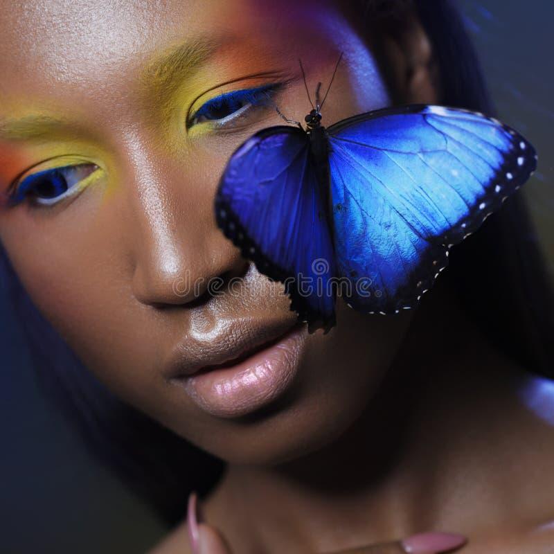 Olhar exótico modelo preto novo e bonito com a borboleta azul brilhante foto de stock