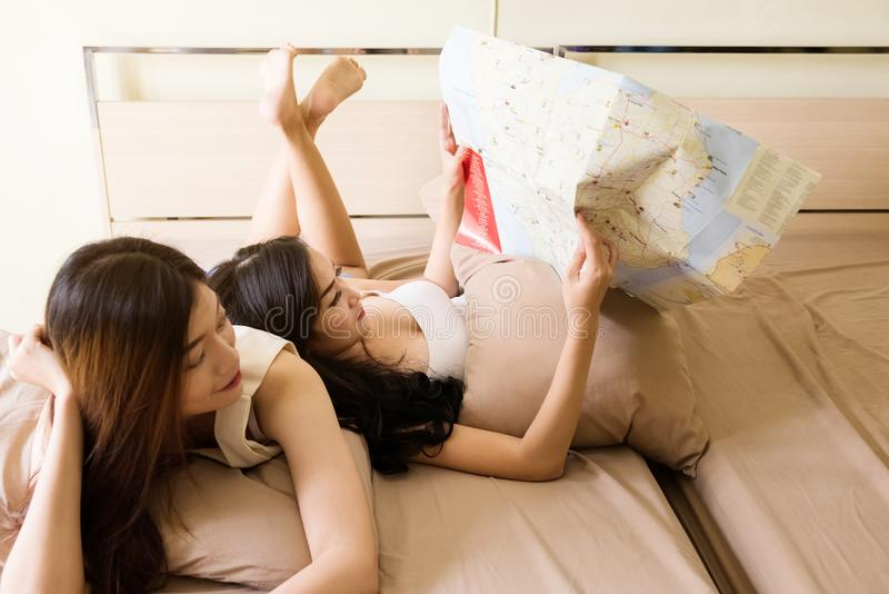 Olhar lésbica dos pares no mapa na cama fotografia de stock