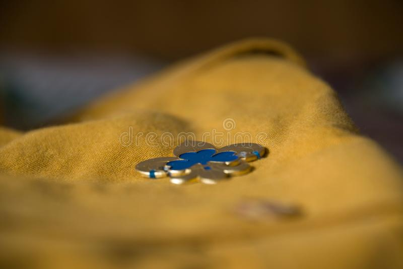 Olhar mais atento ao pino da promessa da escuteira na camisa do escuteiro fotos de stock