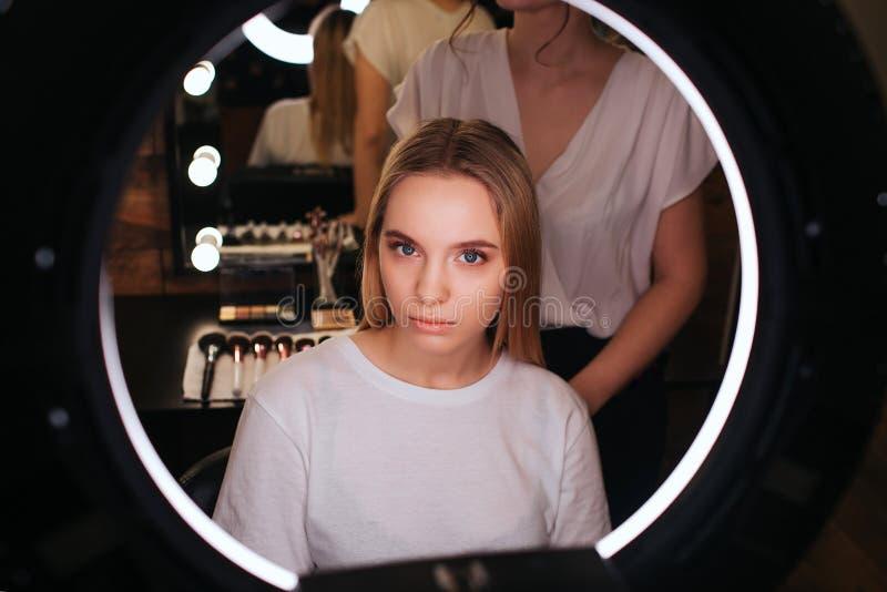 Olhar modelo louro novo sério no espelho na sala da beleza Suporte do cabeleireiro atrás de e trabalho fotografia de stock royalty free