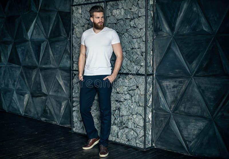 Olhar na moda Comprimento completo do homem novo considerável que olha ausente e que mantém as mãos em uns bolsos ao estar contra imagem de stock
