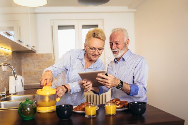 Olhar ocupado dos pares na tabuleta digital ao ter a cozinha deliciosa do caf? da manh? em casa imagem de stock royalty free